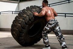 参加十字架适合的锻炼的一个肌肉人通过做轮胎轻碰 免版税库存图片