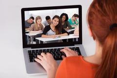 参加在膝上型计算机的女学生网上演讲 免版税库存照片