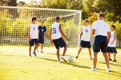 参加比赛的男性高中足球的成员 免版税库存照片