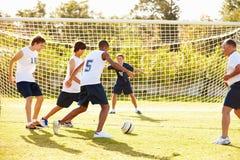 参加比赛的男性高中足球的成员 免版税库存图片