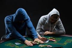参加的打牌者坐在啤牌桌上和所有 免版税图库摄影