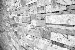 参差不齐的石工大理石砖墙在从边采取的黑白选择聚焦 库存照片