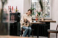 参观与她的小朋友的妇女一个dog-friendly咖啡馆 库存照片