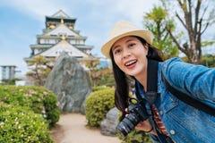 参观单独大阪城堡和采取selfie的旅客 有年轻亚裔的摄影师拿着digicam和自画象与 免版税库存图片