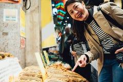 参观地方日本市场的愉快的女孩游人 免版税图库摄影