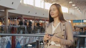 参观城市购物的一名年轻少年旅游妇女的画象使用她智能手机设备和微笑 事务 库存照片