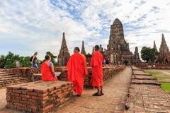 参观废墟Chaiwattanaram寺庙的砖寺庙游人和修士在阿尤特拉利夫雷斯历史公园 免版税图库摄影