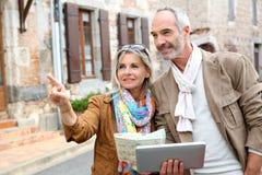 参观有片剂的愉快的夫妇老镇在手上 免版税图库摄影