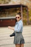 参观有织地不很细石墙纪念碑的可爱的年轻旅游妇女一条pebbled街道,转动对微笑 库存图片