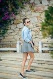 参观有织地不很细石墙纪念碑的可爱的年轻旅游妇女一条pebbled街道,转动对微笑 库存照片