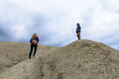 参观泥泞的火山的母亲和儿子 攀登干燥干旱的家庭 免版税库存图片