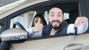 参观的售车行 美丽的家庭是谈话和微笑,当坐在他们新的汽车时 年轻人显示手指 免版税图库摄影