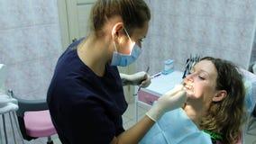 参观给正牙医生设定一名妇女的铁括号有在她的嘴的一牙齿fixator的牙医A医生 股票录像