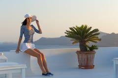 参观著名白色Oia村庄的圣托里尼旅行旅游深色的妇女 免版税库存照片