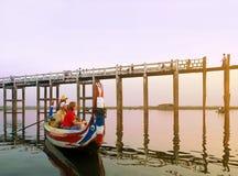 参观著名U-Bein柚木树桥梁的游人在日落 库存图片