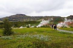 参观Strokkur Geysir的未认出的游人在冰岛 库存图片