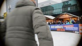 参观Xmas市场的人们在Alexanderplatz在柏林德国 在滑冰在冰的前面年轻和老人 影视素材