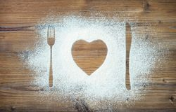 叉子、刀子和板材在心脏塑造,撒粉于洒在裁减附近 库存图片