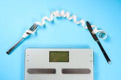 叉子、刀子和标度与一厘米在蓝色背景,饮食,健康生活方式 免版税库存照片
