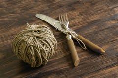 叉子、刀子和螺纹在一张木桌上 免版税库存图片