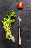 叉子、沙拉叶子和蕃茄在板岩,简单的食物 免版税图库摄影