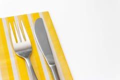 叉子和刀子在一块黄色餐巾 免版税库存照片