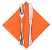 叉子和刀子在橙色布料 库存照片