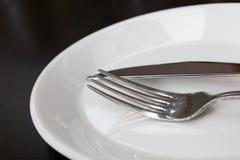 叉子和刀子在白色板材关闭 图库摄影