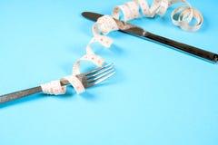 叉子和刀子有一厘米的在蓝色背景,饮食,健康生活方式 库存照片