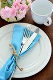 叉子和刀子有盘的,杯子,花在木桌上 免版税库存图片