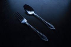 叉子和匙子在一张黑桌上 免版税库存照片