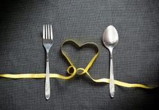 叉子和匙子有由黄色丝带做的心脏形状的在黑色 免版税库存图片