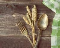叉子和匙子有麦子的耳朵的 库存照片