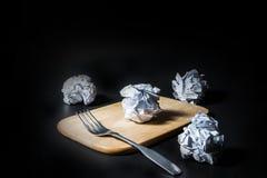 叉子和被弄皱的纸在黑背景 免版税库存照片