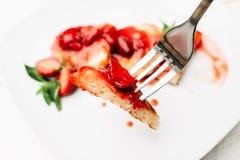 叉子用在被弄脏的背景的草莓薄煎饼 图库摄影