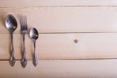 叉子,匙子,在木桌背景的刀子与拷贝plac 免版税库存图片