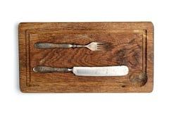 叉子,在葡萄酒样式的刀子在白色背景的一个老切板 免版税库存图片