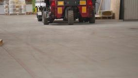 叉架起货车司机在驾驶在棚架行与堆的箱子和包装之间的工厂或仓库 股票录像