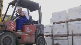 叉架起货车司机在驾驶在棚架行与堆的箱子和包装之间的工厂或仓库 股票视频