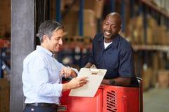 叉架起货车操作员谈话与经理在仓库里 免版税图库摄影