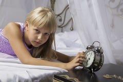 及早唤醒 停止在一张床上的醒一个睡着的女孩闹钟早晨 库存照片
