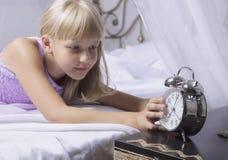 及早唤醒 停止在一张床上的醒一个睡着的女孩闹钟早晨 免版税库存照片