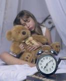 及早唤醒 站立在床头柜上的闹钟 拿着玩具熊在a的床上的醒一个睡着的女孩 图库摄影