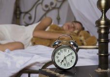 及早唤醒 站立在床头柜上的闹钟 拿着玩具熊在a的床上的醒一个睡着的女孩 免版税库存照片