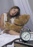 及早唤醒 站立在床头柜上的闹钟 拿着玩具熊在a的床上的醒一个睡着的女孩 免版税库存图片