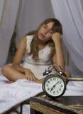 及早唤醒 站立在床头柜上的闹钟 醒一个睡着的女孩在背景的床上 免版税库存照片