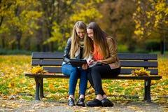 及早温暖秋天 两个迷人的女孩坐一条长凳在秋天公园 免版税图库摄影