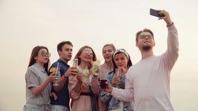 友好和快乐的公司,与美丽的鸡尾酒的使叮当响的玻璃在照相机智能手机 都市的夏天 股票录像