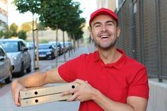 友好和逗人喜爱的比萨交付人 免版税库存照片