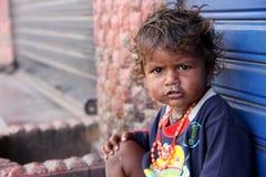 友好无家可归的女孩的看起来逗人喜爱和有连续鼻子,穿戴肮脏的衣裳坐街道 免版税图库摄影